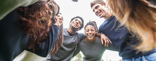 Multiracial group of friends embraced in a circle